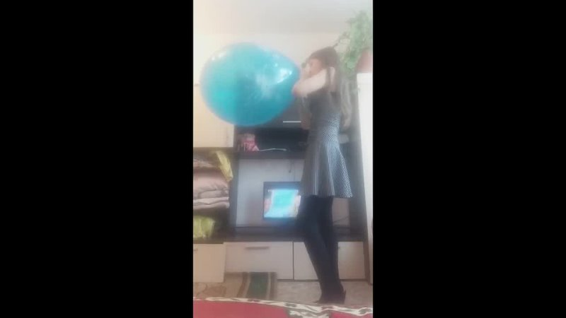 Young woman blows up a large balloon in front of a shitty tv until it pops sadlife