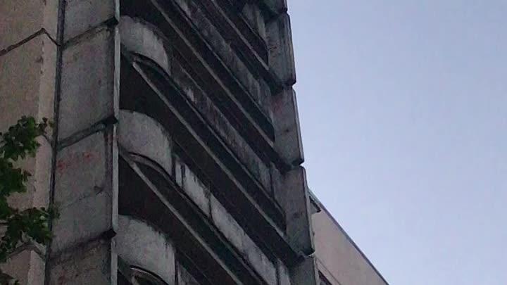 На Просвещения 36/141 мужчина стоит на внешней стороне балкона.