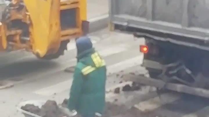 На перекрёстке Прядильного и Люблинского переулков, рабочие грузят в садовую тележку экскаватором ...