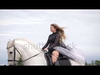 stock-footage-beautiful-blonde-girl-with-black-dress-rides-a-white-horse-in-slow-motion