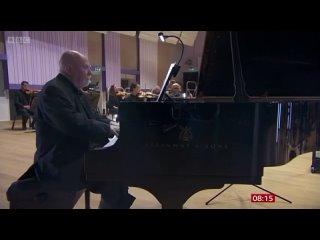 Пол Харви играет свое произведение с симфоническим оркестром на сцене.