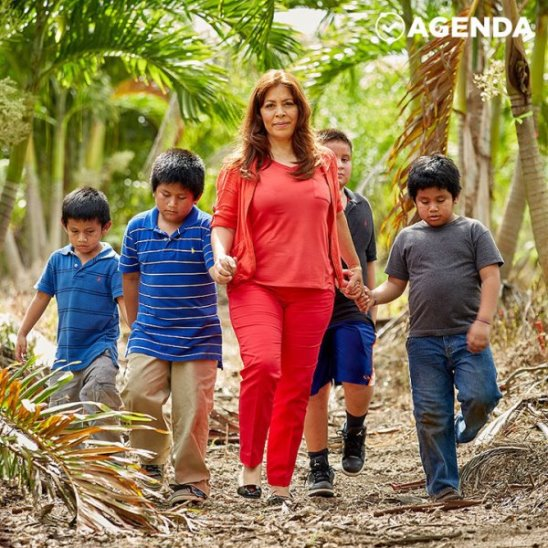 Женщина помогает детям мигрантов