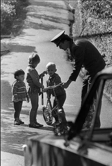 Милиционеры ремонтируют сломанный велосипед плачущей девочке.